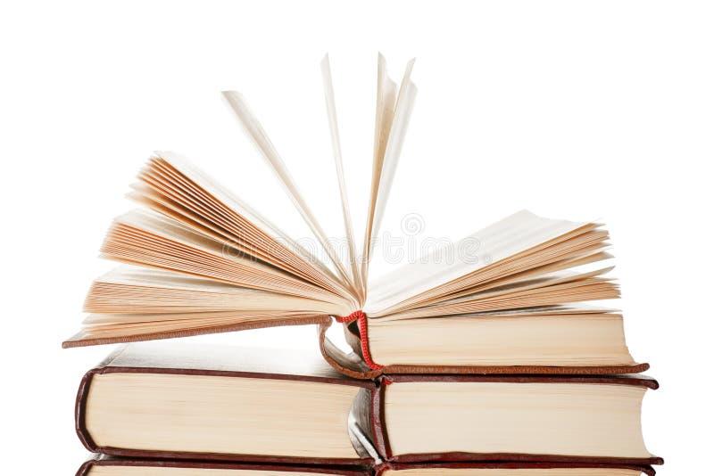 Открытая книга поверх кучи книг изолировала стоковое фото