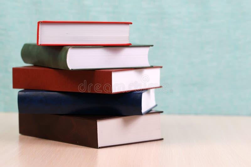 Открытая книга, стог книг hardback на деревянном столе стоковая фотография rf