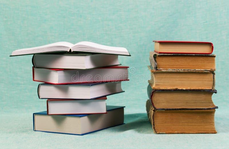 Открытая книга, стог книг hardback на таблице E r стоковые фото