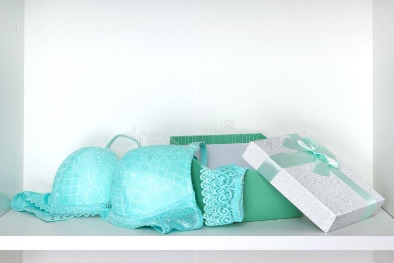 Открытая подарочная коробка с женское бельё установила на белую полку внутри шкафа стоковые фотографии rf
