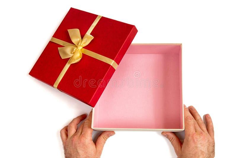 Открытая подарочная коробка с смычком ленты золота в руках ` s людей, изолированных на белизне стоковые фотографии rf