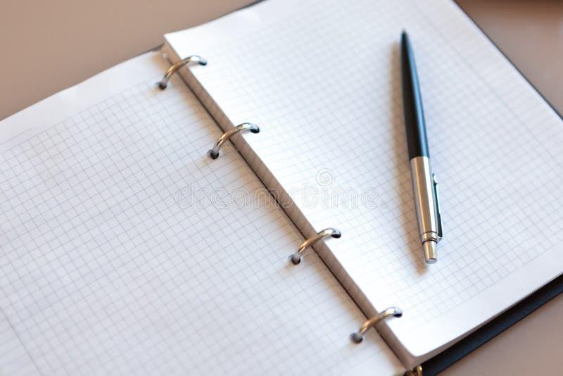 Открытая тетрадь с ручкой лежа на ей на бежевом рабочем столе Листы блокнота на серебряных кронштейнах, автоматической шариковой  стоковые фото