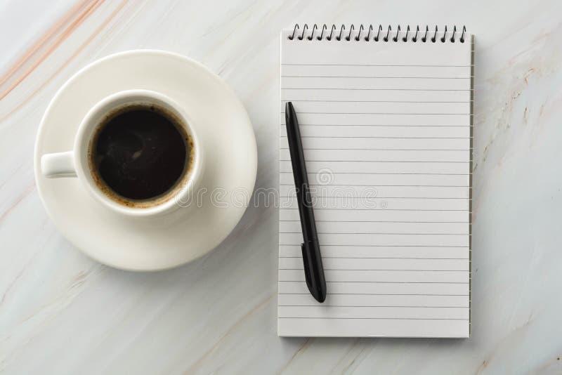 Открытая тетрадь с чашкой кофе на мраморном столе Рабочее место, таблица работы r стоковые изображения rf