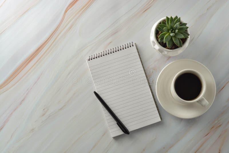 Открытая тетрадь с чашкой кофе, суккулентным заводом на мраморном столе Рабочее место, таблица работы r стоковое фото