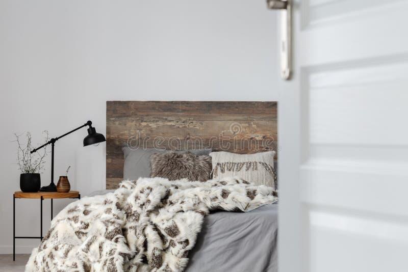Открытые двери до серой элегантной спальни интерьер с загородным дизайном, копировать пространство на пустой стене стоковые фото