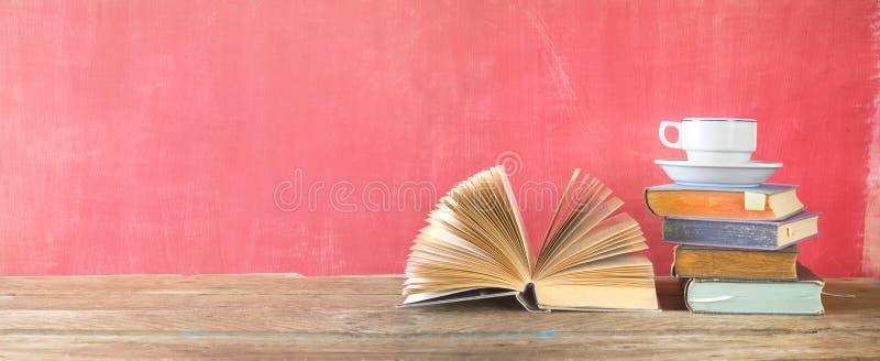 Открытые книга и стог книг hardback с чашкой кофе стоковая фотография rf