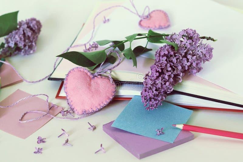Открытые книги, сердца закладок, бумага, карандаши, ветви цветков сирени на таблице стоковое фото rf