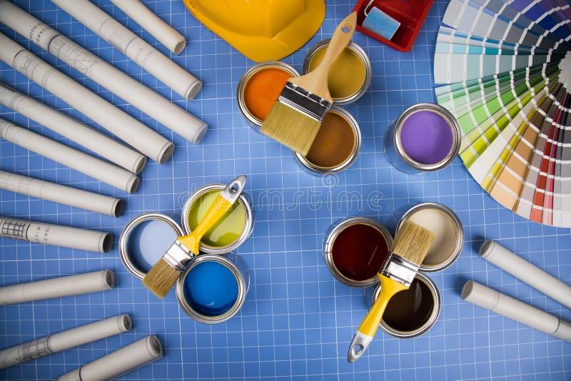 Открытые консервные банки краски, щетки, голубой предпосылки стоковое изображение