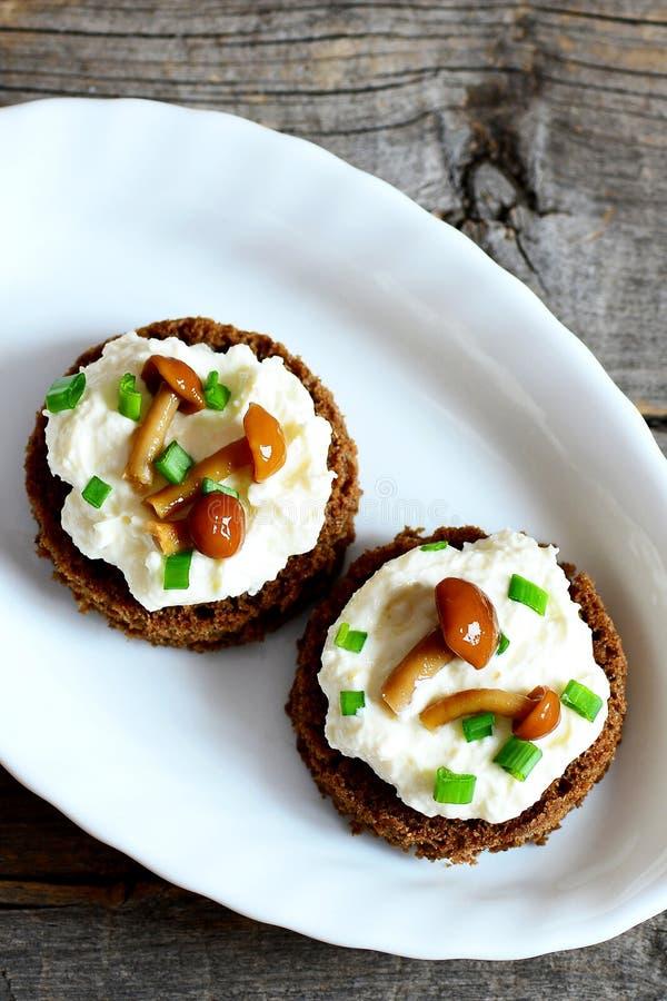 Открытые сандвичи с мягким сыром, грибами лисички и зелеными луками на плите на винтажной деревянной предпосылке стоковое фото rf