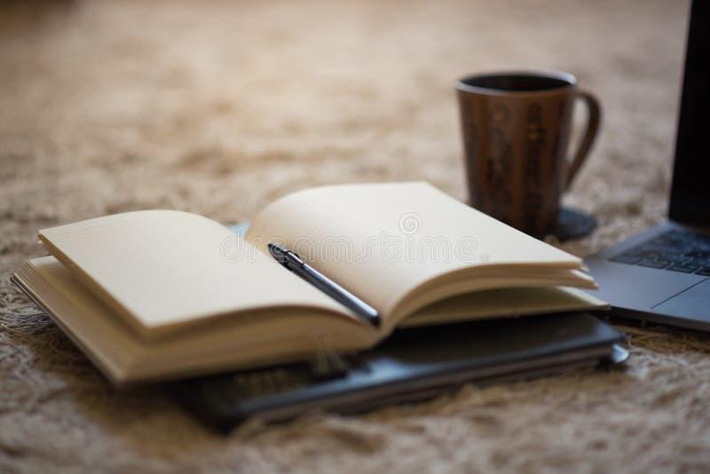 Открытый журнал с ручкой и теплыми светлыми освещающими пустыми страницами стоковое изображение