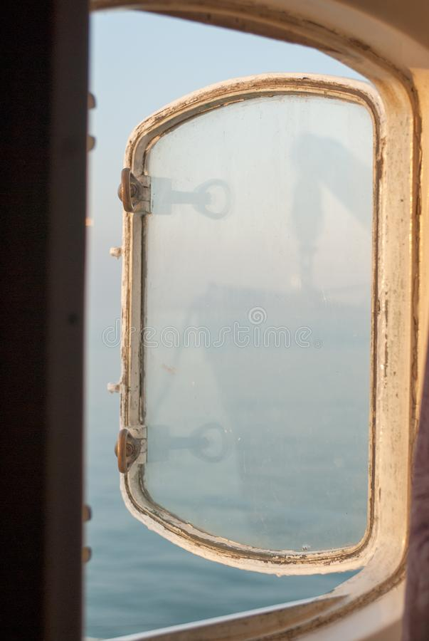 Открытый иллюминатор на корабле с отражением шлюпки вися на кабелях стоковое изображение
