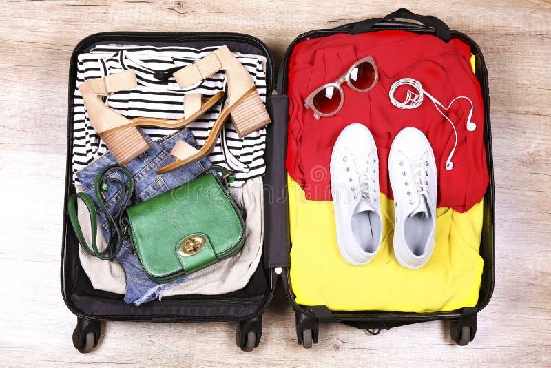 Открытый чемодан вполне штабелированный с различными одеждами стоковое изображение rf
