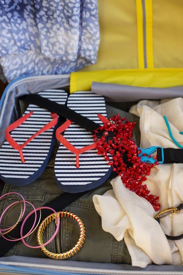 Открытый чемодан полно упакованный с одеждой и аксессуарами сложенных женщин стоковое фото