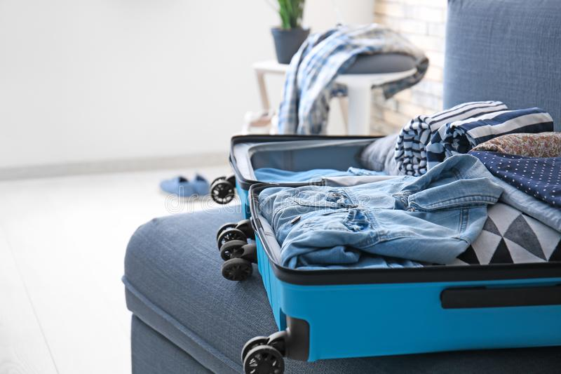 Открытый чемодан с одеждами на софе стоковые изображения rf