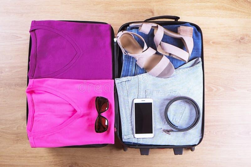 Открытый чемодан упакованный для путешествовать, на деревянном взгляд сверху пола, конец вверх Концепция сумки перемещения стоковое фото