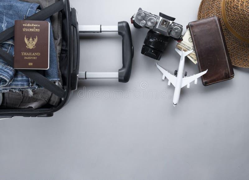 Открытый чемодан упакованный для путешествовать с паспортом Таиланда на серой предпосылке - концепции перемещения - изображение стоковая фотография