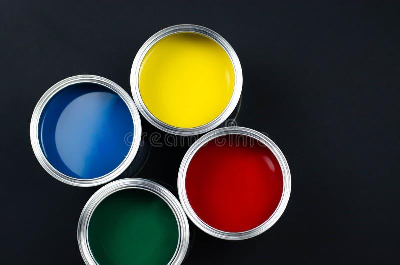 4 открытых консервной банки краски на черной предпосылке стоковые фото