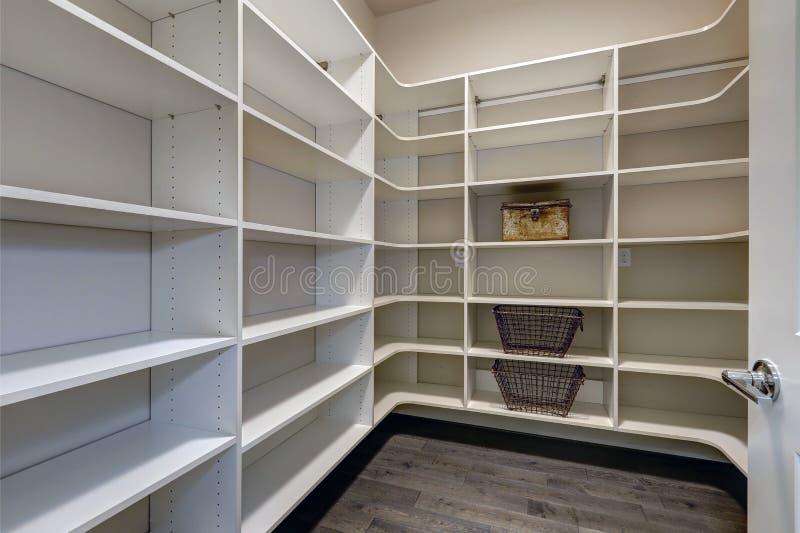 Открыть дверь для того чтобы опорожнить комнату кладовки с белыми полками стоковые изображения rf