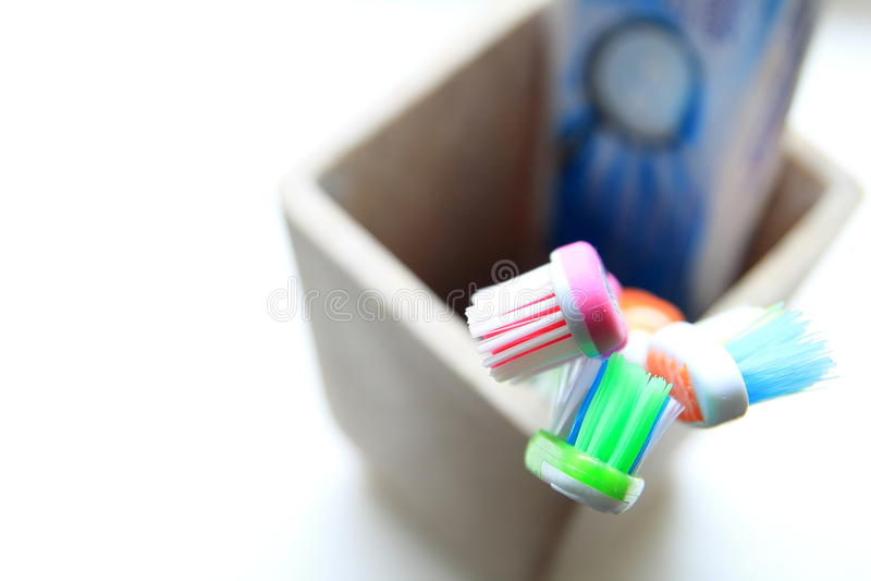 Отмелый DOF снял 3 зубных щеток и зубных паст в tumbler глины в свете утра стоковое изображение rf