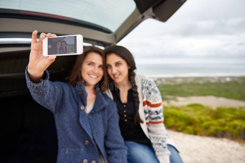 Отображайте на умном телефоне женских друзей принимая selfie стоковая фотография