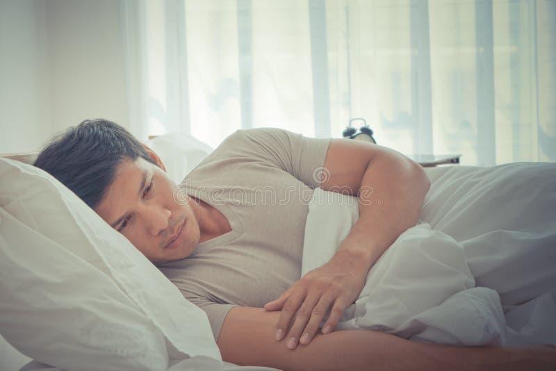 Отожмите позднее утро человека лежа на кровати стоковое фото