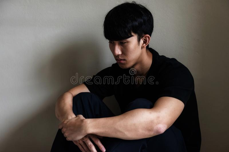 Отожмите пристрастившийся человека сидите около стены стоковые изображения