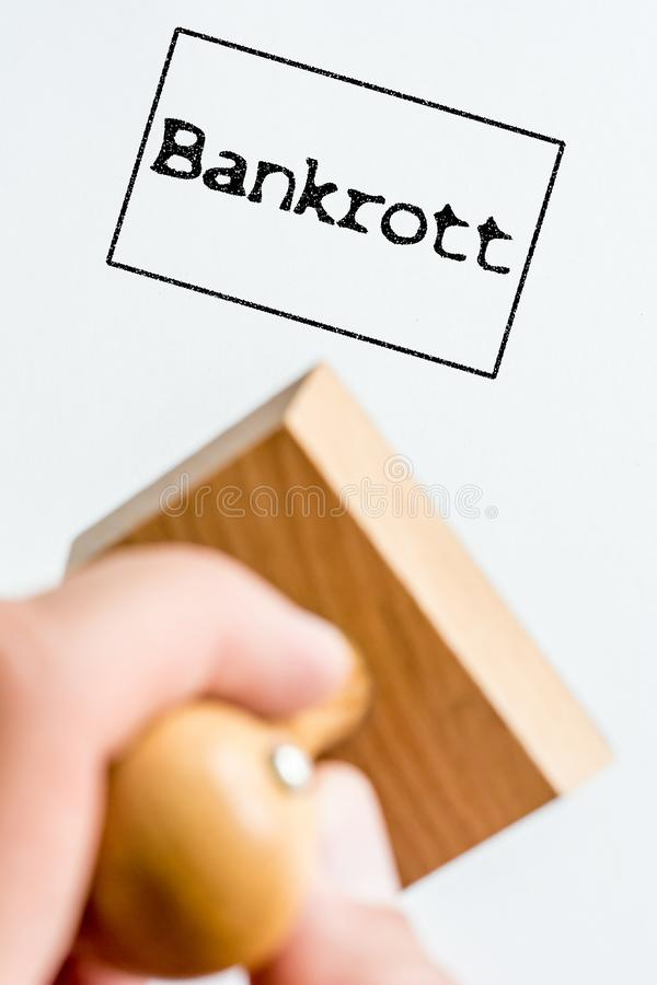 Отпечаток печати на белой бумаге на теме финансов с немецким словом для банкротства стоковое изображение