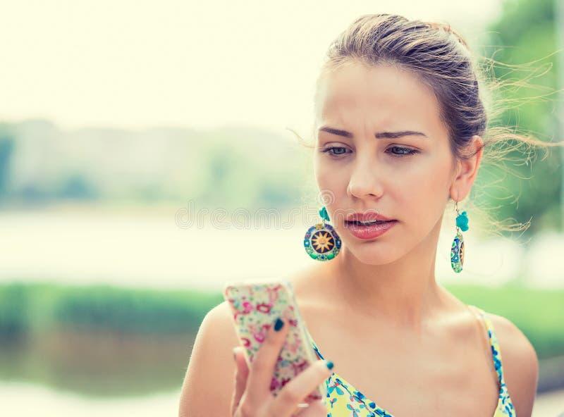Отправка СМС расстроенной унылой женщины говоря на раздражанном телефоне стоковое фото