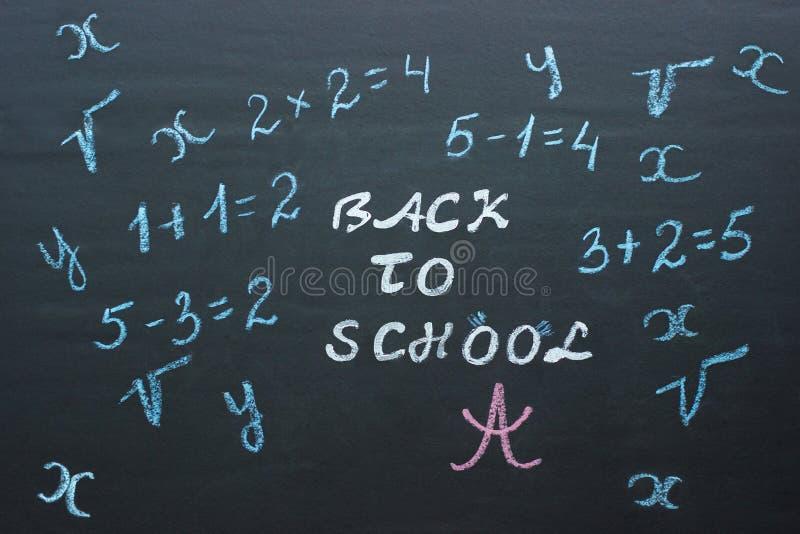 Отправьте СМС назад к школе и математически примерам на черное chalkboar стоковое изображение rf