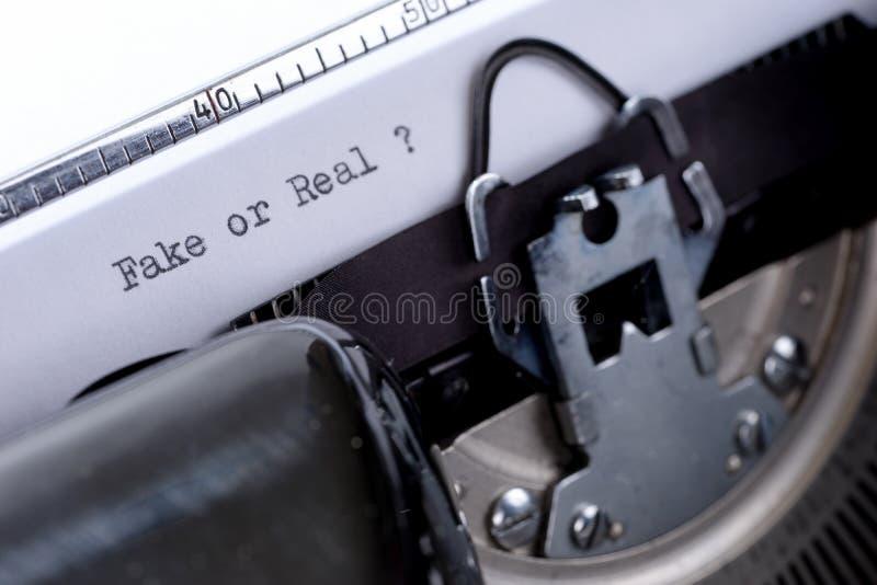 Отправьте СМС фальшивка или реальное написанные на старой машинке стоковое изображение rf
