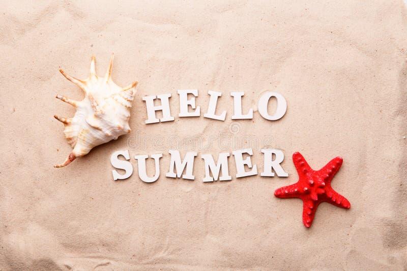 Отправьте SMS здравствуйте лету от белых писем и раковины и морских звёзд моря на песке стоковые фотографии rf