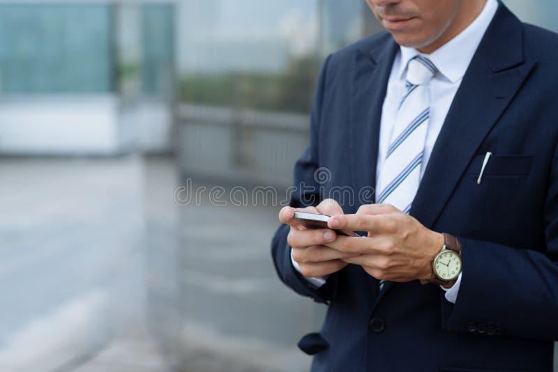 Отправляя СМС бизнесмен стоковые фото