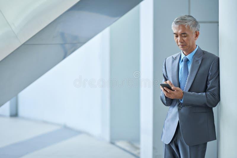Отправляя СМС бизнесмен стоковое фото