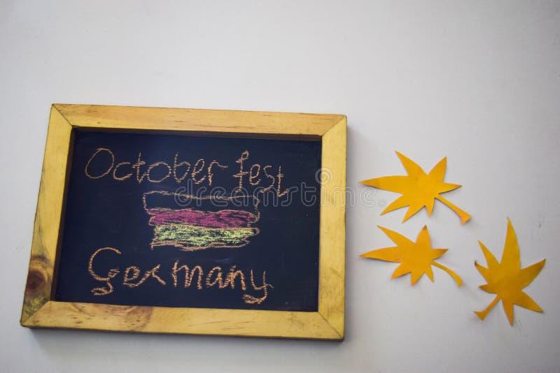 Отпразднуйте фестиваль в октябре - штыри одежд на серой/белой предпосылке и доске с ` Германии фестиваля в октябре ` лозунга стоковая фотография rf