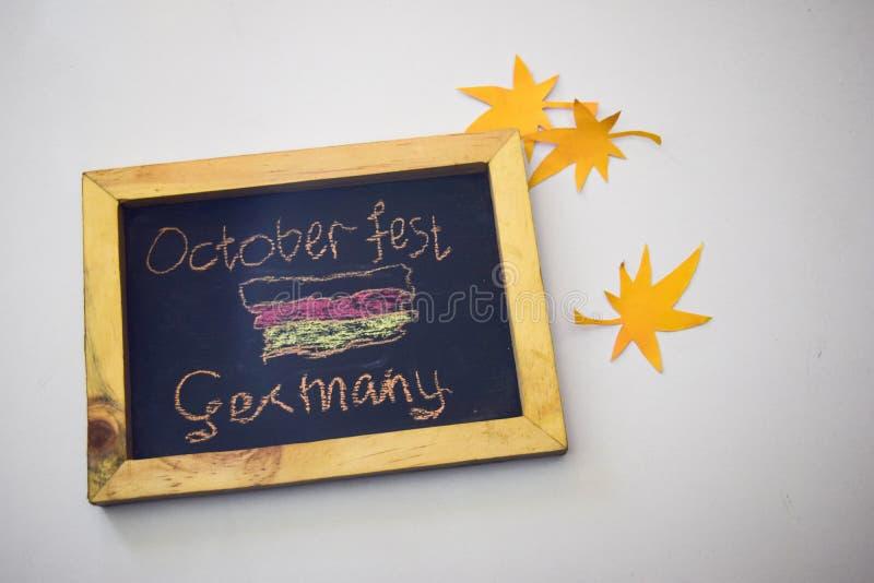 Отпразднуйте фестиваль в октябре - штыри одежд на серой/белой предпосылке и доске с ` Германии фестиваля в октябре ` лозунга стоковое фото rf