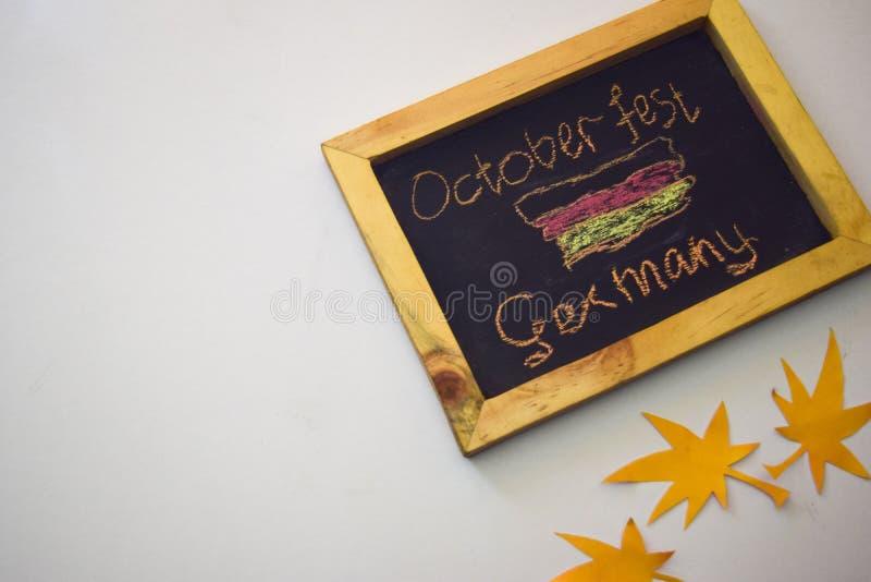 Отпразднуйте фестиваль в октябре - штыри одежд на серой/белой предпосылке и доске с ` Германии фестиваля в октябре ` лозунга стоковое изображение rf