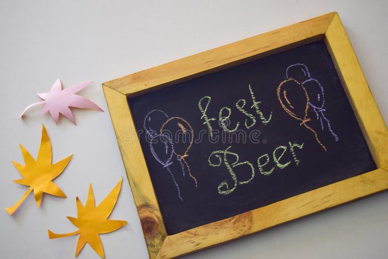 Отпразднуйте фестиваль в октябре - штыри одежд на серой/белой предпосылке и доске с ` пива фестиваля ` лозунга стоковые фотографии rf