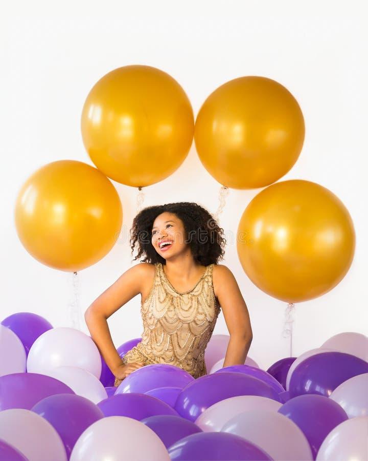 Отпразднуйте полезного времена работы! Привлекательная смеясь над молодая женщина празднует с воздушными шарами стоковая фотография rf