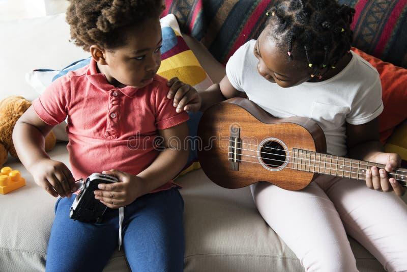 Отпрыски тратя время совместно играя гитару стоковые изображения
