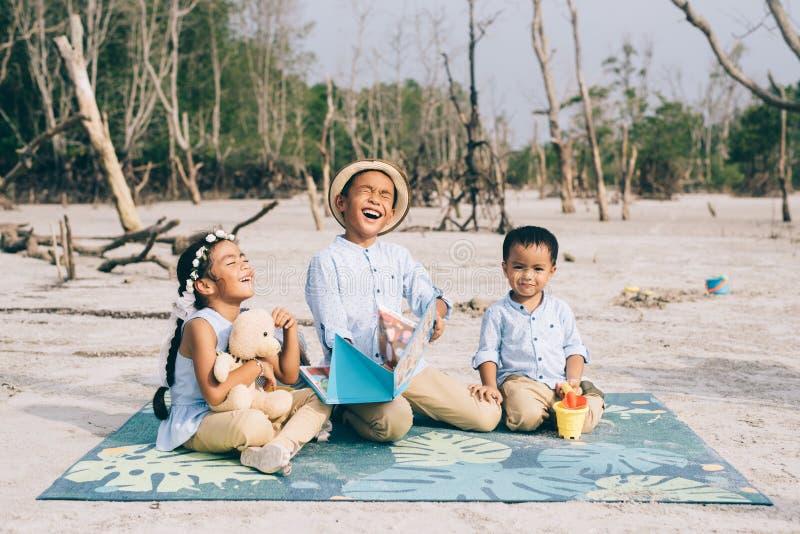 Отпрыски читая и смеясь над совместно outdoors носить вскользь стоковое фото