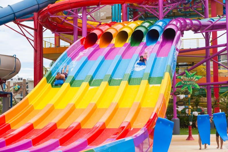 Отпускники наслаждаясь их временем, сползая вниз с гигантского слайдера воды стоковые фото