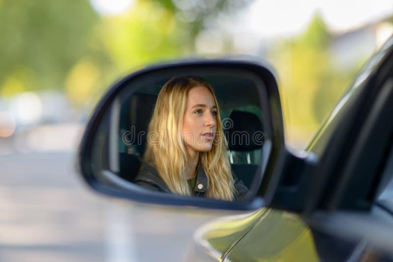 Отражение белокурой женщины в зеркале крыла автомобиля стоковые изображения rf