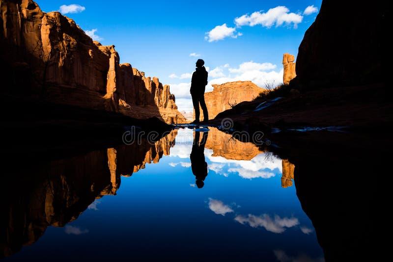Отражение в спокойном озере в пустыне южной Юты Отражение человека готовя пруд так же, как красные башни утеса и стоковые изображения rf