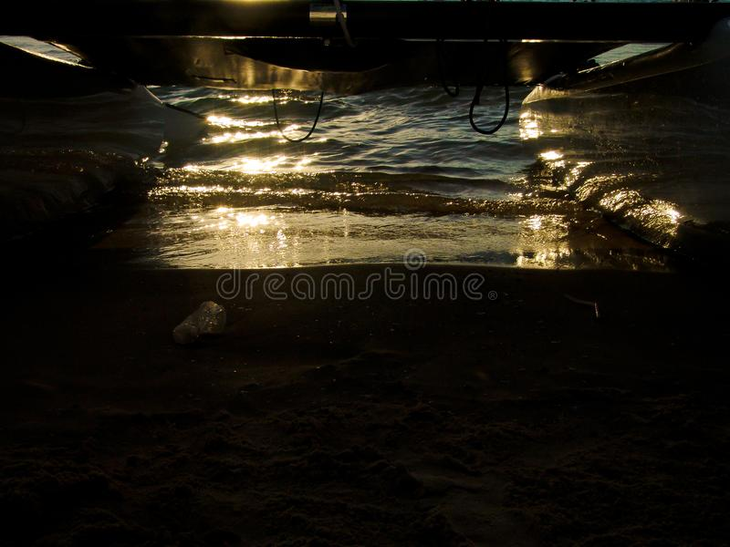 Отражение захода солнца на влажном песке над песчаным пляжем в океане, под шлюпкой доски прибоя ветра стоковое изображение rf