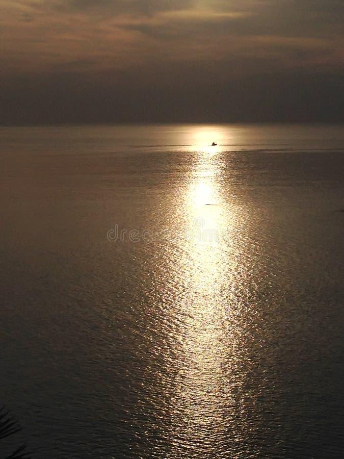Отражение захода солнца и солнечного света моря пропуска корабля стоковое изображение
