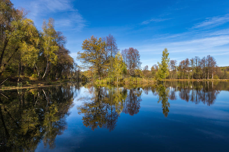 Отражение малых деревьев в озере под голубым небом с прерывистыми облаками стоковые фотографии rf