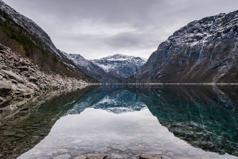 Отражение Норвегия воды горы озера Trolltunga стоковые фотографии rf