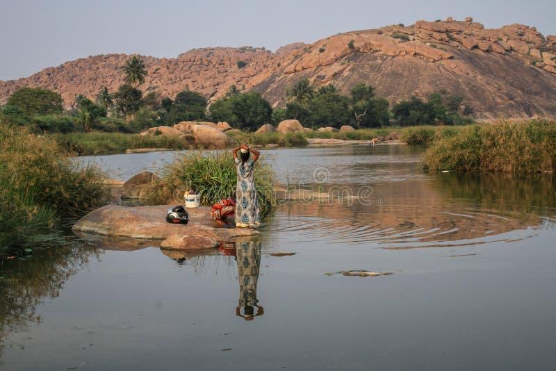 Отражение рекой Tungabhadra, 2 женщины моя блюда, Hampi, Karnataka, Индию стоковое изображение