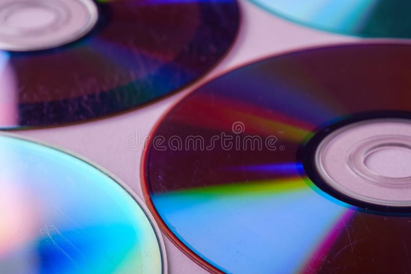 Отражение рефракции рассеивания диска компакт-диска CD DVD текстуры светлых цветов на розовом конце предпосылки вверх стоковое фото rf