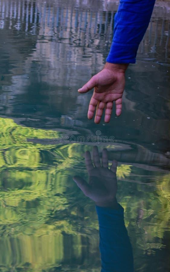 Отражение руки в воде на историческом пруде воды в Кашмире Индии стоковое фото